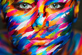 Portrait of the bright beautiful girl with art colorful make-up and bodyart