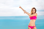 Woman in swim posing on beach over sea background at summer pointing on copy space.