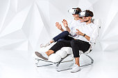 A young couple wearing VR headsets sitting on white chair in a room with white walls and floors