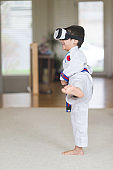 Young Native American in martial arts uniform and using 3D glasses practices his kicks in living room