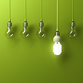 One hanging energy saving light bulb glowing different standing out from unlit incandescent bulbs with reflection on green background, leadership and different creative idea concept