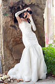 Beautiful bride in wedding dress taking photos with professional camera