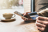 Man shopping online with smart phone and credit card