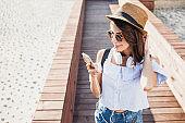 Happy trendy girl using smart phone