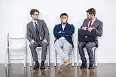 young businessmen sitting on chairs in waiting room, business concept