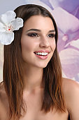 Young attractive woman with flowers in her hair posing in studio