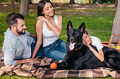 smiling family resting together on blanket on picnic at countryside