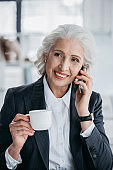 senior businesswoman using smartphone and drinking coffee at workplace in office