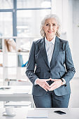 Smiling senior businesswoman standing in office and looking at camera