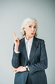 portrait of curious senior businesswoman with arm up isolated on grey