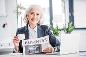 Smiling senior businesswoman drinking coffee and reading newspaper at workplace