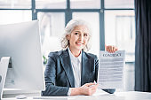 portrait of smiling businesswoman sitting at workplace and pointing at contract