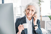 Smiling senior businesswoman drinking coffee and talking on smartphone at workplace