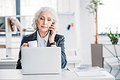 Serious senior businesswoman holding coffee cup and talking on smartphone