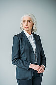 pensive senior businesswoman in suit looking aside isolated on grey