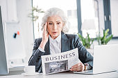 Shocked senior businesswoman in formal wear reading newspaper at workplace