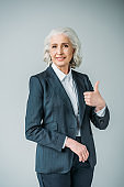 smiling senior businesswoman in suit showing thumb up isolated on grey