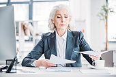 portrait of confident senior businesswoman doing paperwork at workplace