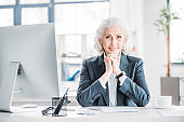 Beautiful senior businesswoman sitting at a workplace and smiling at camera