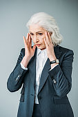 senior businesswoman in suit having headache isolated on grey
