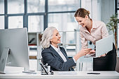 Two smiling businesswomen talking and using laptop at workplace