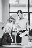 businesswoman and her boss working with documents in office, black and white