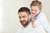 little son with young father spending time at home