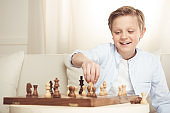 portrait of cheerful little boy playing chess alone at home