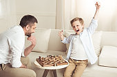 side view of boy celebrating success in chess game with father near by