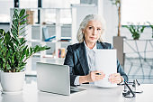 senior businesswoman working with documents and laptop while sitting at workplace in office
