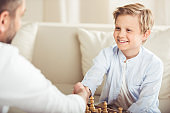 father and son shaking hands after playing chess board game