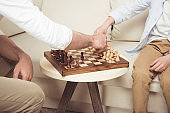 Cropped shot of father and son sitting and playing chess at home