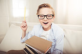 Happy little boy in eyeglasses holding pile of books and pointing up with pencil