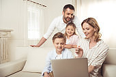 Happy family with two adorable children sitting together and using laptop at home