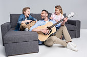happy family playing on guitar and singing, spending time together while sitting on sofa