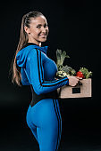 Smiling sporty woman holding basket with fresh vegetables, healthy living concept