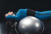 Attractive young sportswoman exercising with fitness ball isolated on black