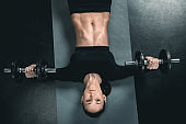 young fitness woman training with dumbbells and lying on mat