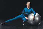 Smiling young sportswoman stretching with fitness ball