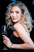Gorgeous young blonde woman holding champagne glass and looking away