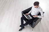 Top view of man with laptop in armchair