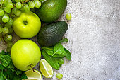 Selection of green vegetables and fruits on a gray concrete back
