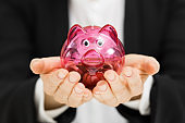 business profit savings concept - woman holding piggy bank in hands