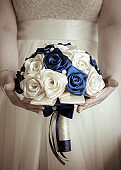The bride's bouquet in hands on background of wedding dress