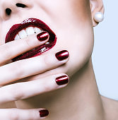 Part of face close up, red lips and nails