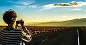 Young man, travelling hipster, taking a shoot with the smartphone on the desert road in Nevada at Sunset