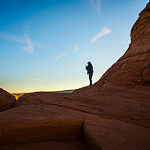 The young hipster man, traveler and hiker, admiring the sunrise in the red canyon near by Delicate Arch, Utah, at sunrise