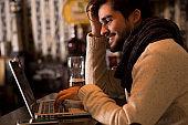 Man using laptop while sitting at cafe.