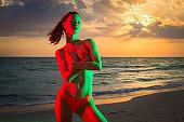Beuatiful young woman at the beach sunset