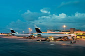 Passenger airplane on runway near the terminal in an airport at night. Airplane parking at departure gate in airport.